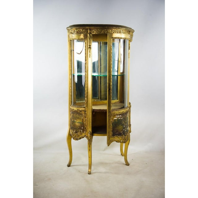 Display your prized glassware and china in this early 20th c. French Louis XV giltwood curio cabinet. The elegant acanthus...