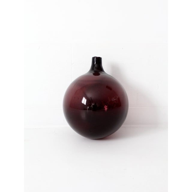 A vintage glass float. The large old fishing float is purple and features a bottleneck.