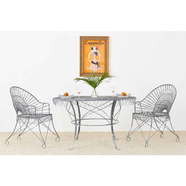 Fantastic French iron and wire patio garden dining table having a round frame. The wrought iron form is embellished with...
