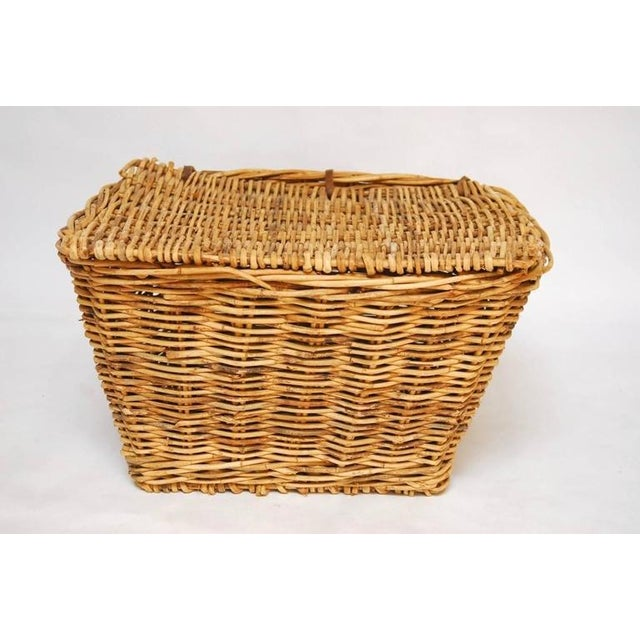 Grand French woven rattan harvest basket with handles featuring a lidded top with leather strap hinges. Large-scale would...