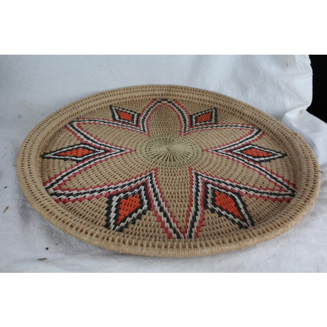 Handwoven textile swirled tribal platter with floral design in tan, red, orange, white, and black. Raised lip for serving.