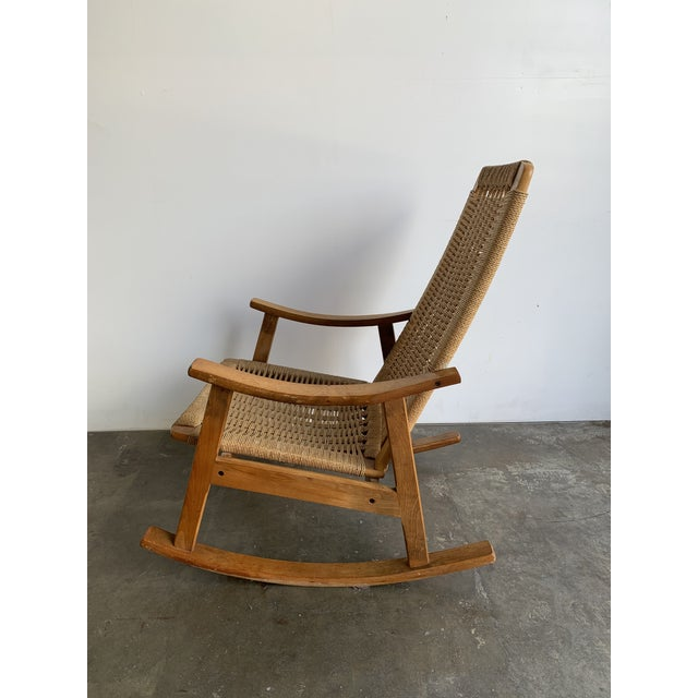 Mid century rocking chair in wood and webbed roping. This item is in good original vintage condition. Roping is strong and...