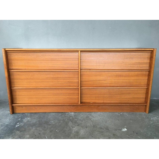 Exquisite danish modern manufacturing showcased in this teak double dresser with six drawers featuring built in top lip...