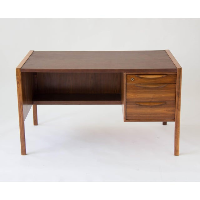 A modest walnut desk from Jens Risom with three drawers on the right-hand side, and a leather writing surface. Each drawer...