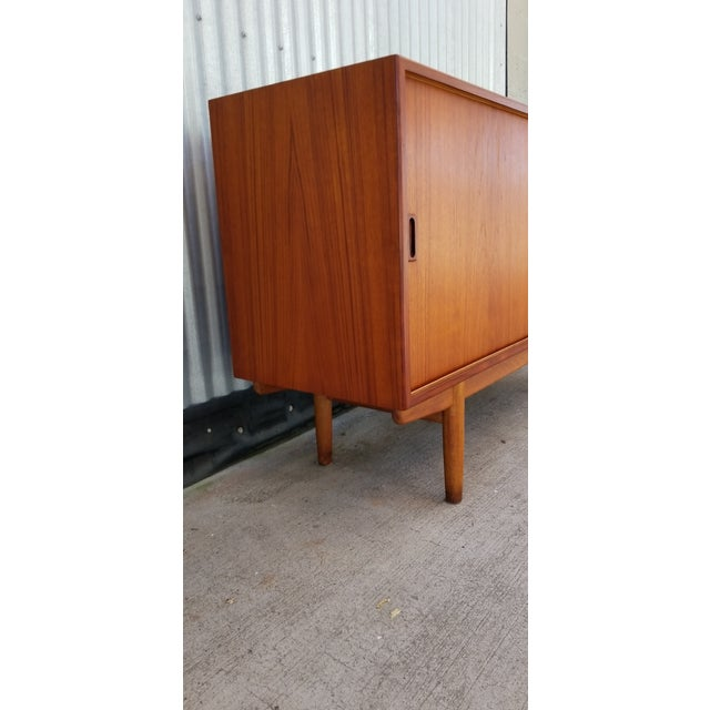 A teak Danish Modern credenza designed by Borge Mogensen, Denmark, circa 1960. Features sliding doors, adjustable shelf...