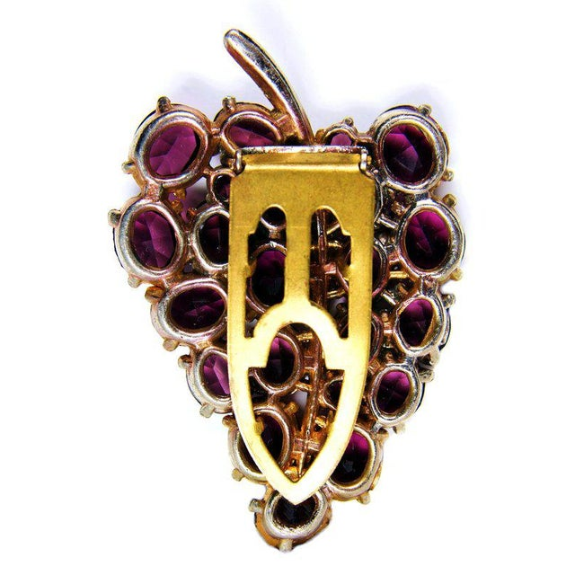 Very pretty goldtone metal dress clip prong set with large open-back purple faceted glass stones. It's in a lovely leaf-...