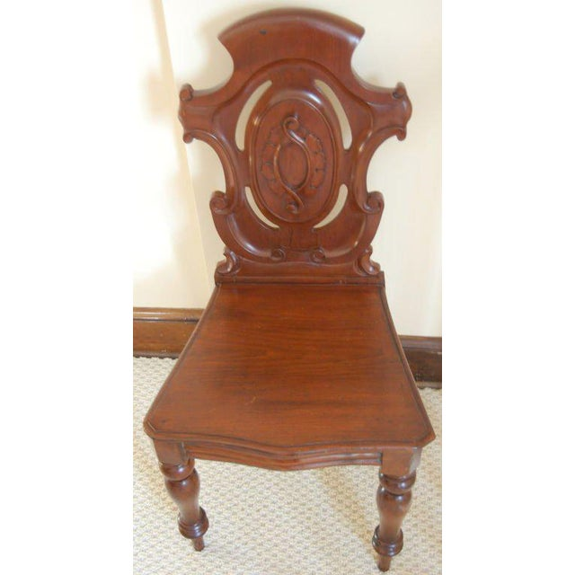 Pair of late 19th century English mahogany shield back carved and decorated hall chairs, the backs with a center medallion...