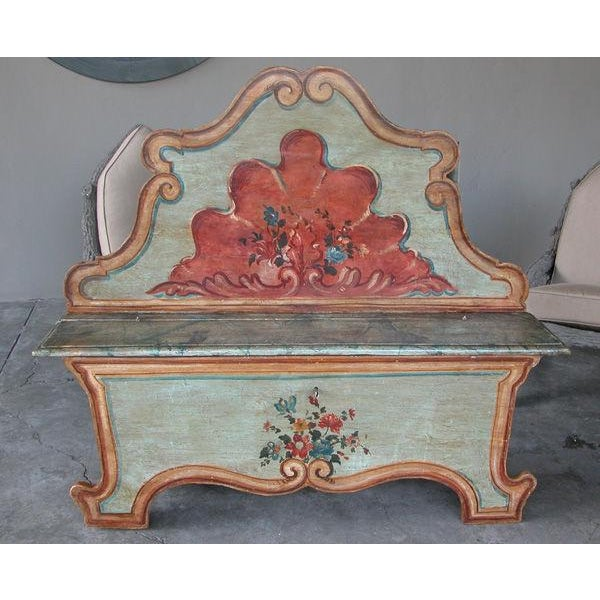 A fanciful Venetian baroque style pine polychromed highback bench; with high cartouche-shaped back centering an over-...