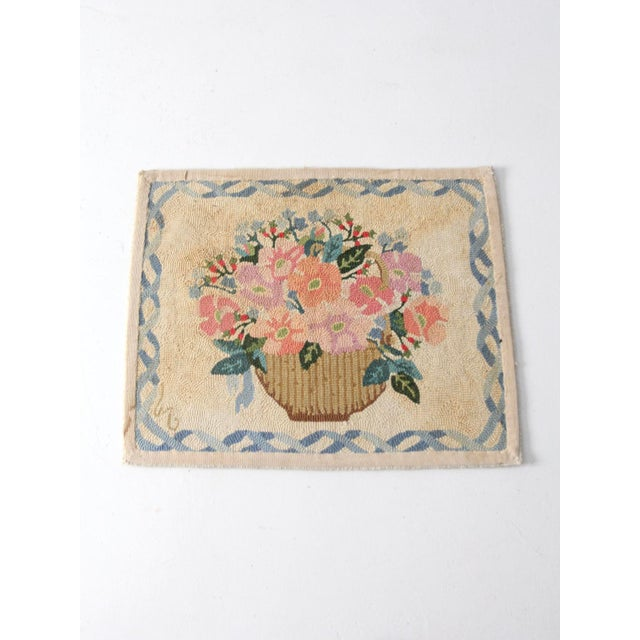 This is a vintage hand hooked rug from the early 20th century. The cream wool floor mat features a floral bouquet pattern...