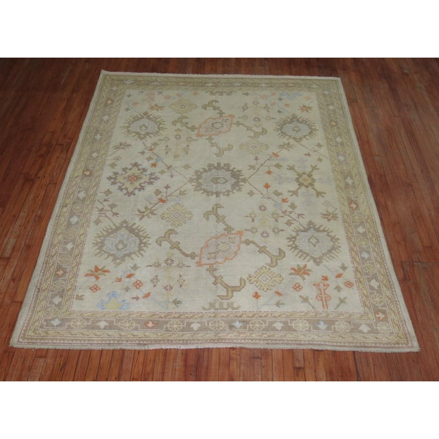 An early 20th century ivory field antique Turkish Oushak rug. This piece is a true antique, one of a kind rug that has...