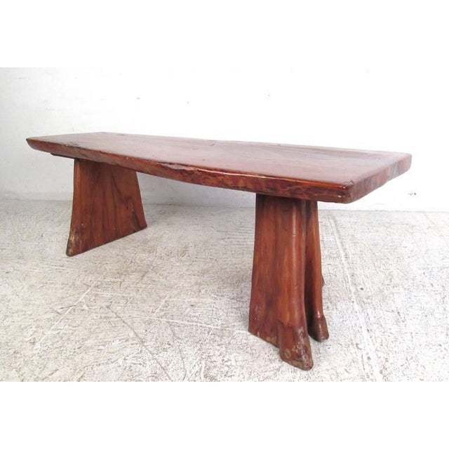 This unique vintage bench is crafted from live edge wood and covered with a unique finishing lacquer for added durability....