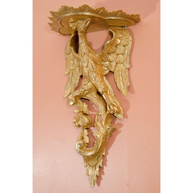 Pair of George III style Rococo giltwood brackets, the supports carved as phoenix birds atop C-scrolls with fruit pendants.