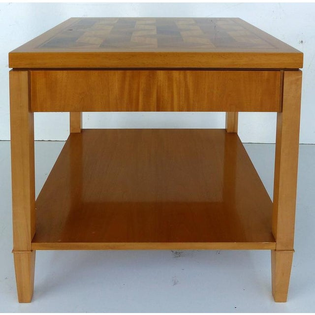 A Baker Furniture side table with inlaid geometric pattern designs. Finished on all sides. Retains the makers' tag within...