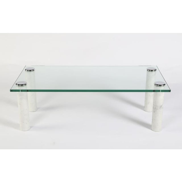 Chrome caps attach the thick rectangular glass top to the cylindrical white marble legs of this 1970s Pace Collection...