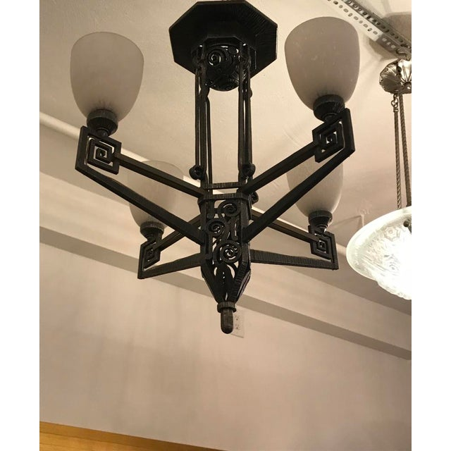 Beautiful French Art Deco chandelier in the style of Edgar Brandt. Having intricate deco hand-forged iron frame details....