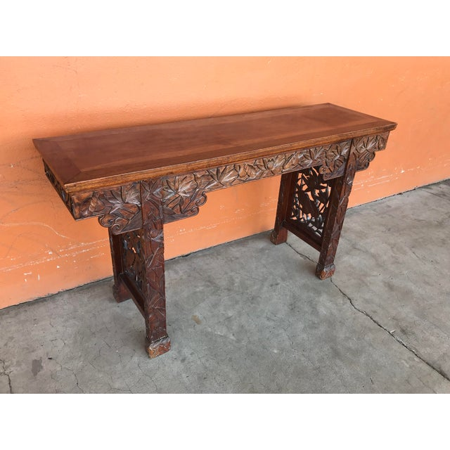 Chaines altar table carved upon all four sides with floral elements. Wood appears to be teak. 59 inches wide, 17 deep and...
