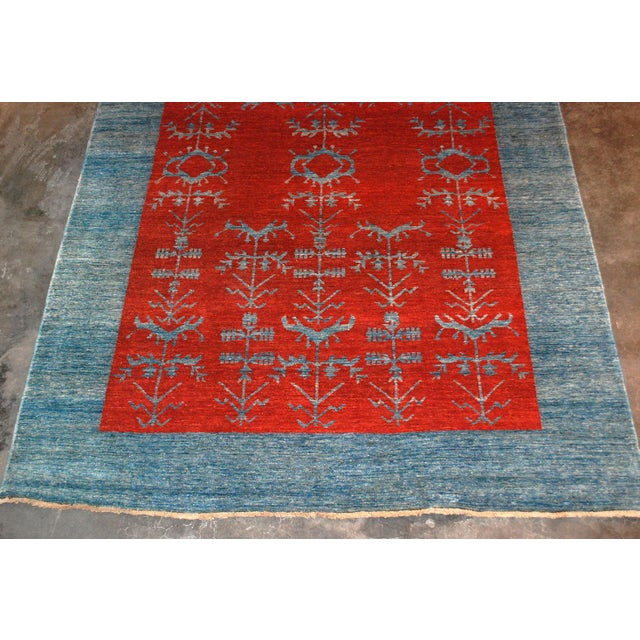 Hand-knotted Gaba wool rug. Blue striaed background with striking red pattern through center.