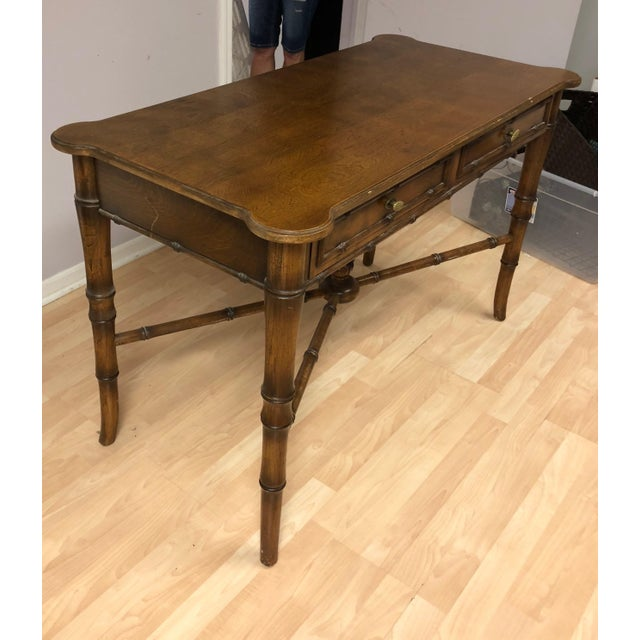Vintage, Regency-style writing desk/console table. Faux bamboo in warm wood finish. The desk features top with rounded...