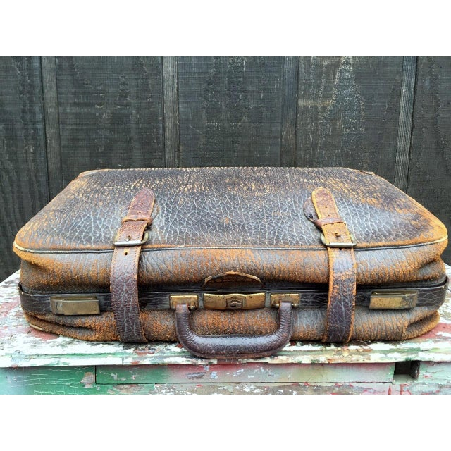 Vintage leather suitcase that buckles externally. This suitcase has aged beautifully; the worn leather only enhances the...