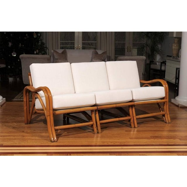 An exceptional vintage modern three-seat sofa, circa 1950. Stout, expertly crafted rattan frame construction. Beautiful...