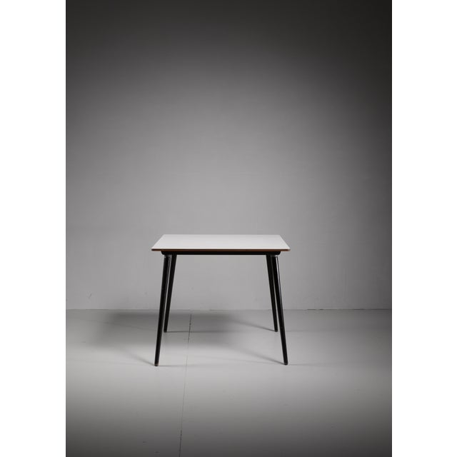 A small wooden model DTW-40 table, designed by Charles Eames for Herman Miller. It has a white laminated top with...