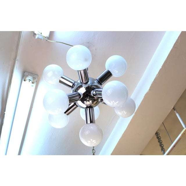 A molecular style chandelier with a chrome structure and white glass globes, made during the Atomic age. The piece is in...
