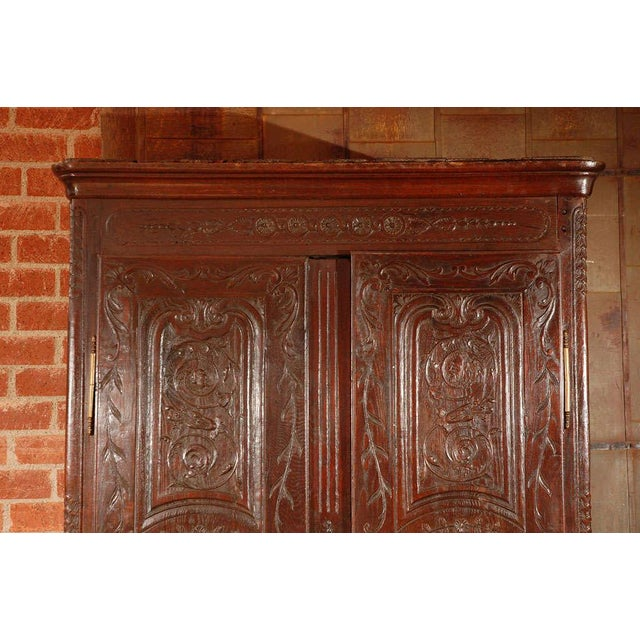 In a shape and form very typical of the Regency and early LXV periods, this armoire has likely had the carved decorative...