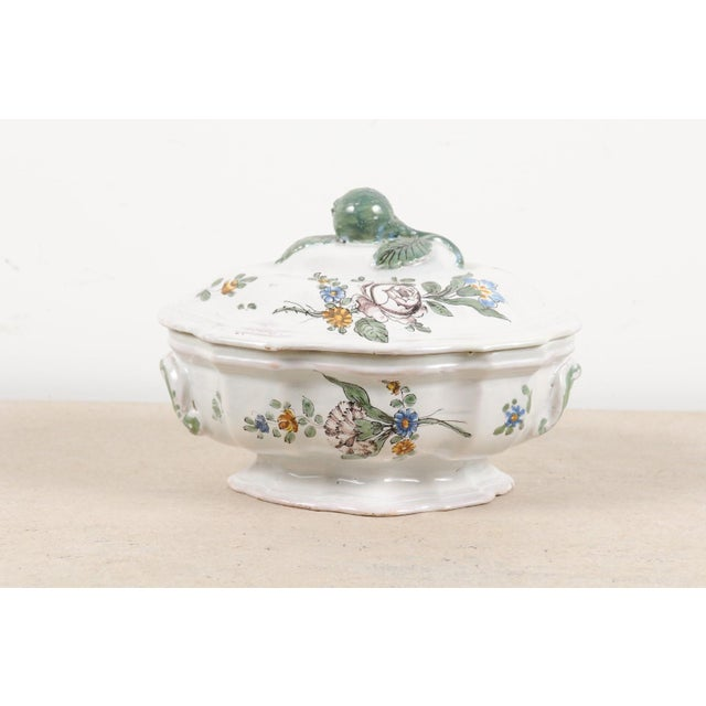 A French faïence mid-18th century oval-shaped soup tureen from Bordeaux with floral decor. Created in Southwestern France...