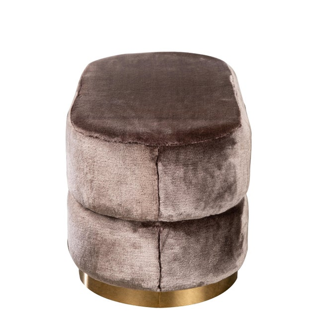 """Playful oval ottoman with gold base. Material : Faux fur , stainless steel Colors: Mink, gold Measurements: 37.5""""l x 18"""" w..."""