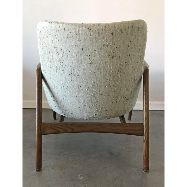 A stunning Ib Kofod Larsen lounge chair. This early chair has been reupholstered in a gorgeous cream, nubby fabric with...