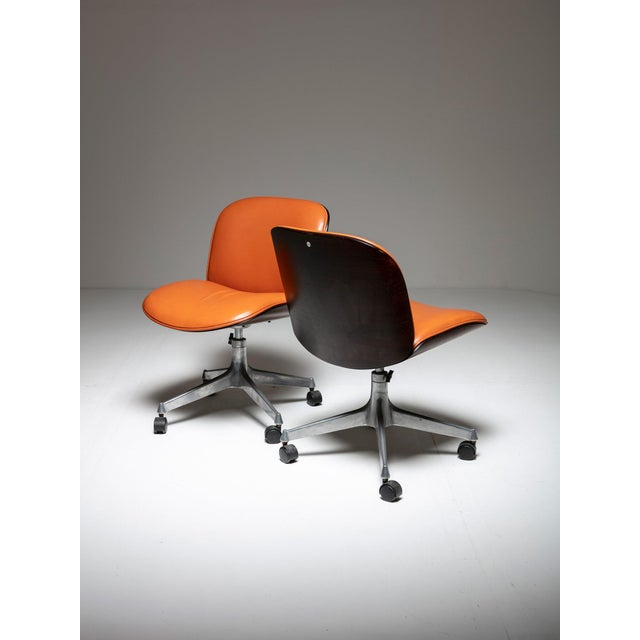 Pair of small swiveling office chairs by MIM. Beautiful wood shell, cognac upholstery and aluminum base.