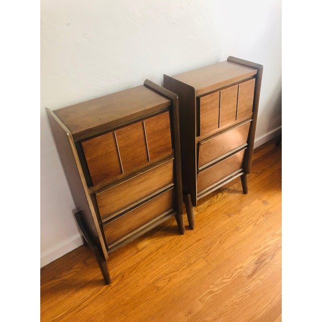 A pair of unique mid century nightstands. Each features 2 large lower drawers and exposed leg detailing. A fold out shelf...