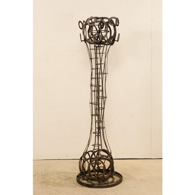 A tall French sculptural iron art piece in a motif of rings from the 1930s-1940s. This unique sculpture from France,...