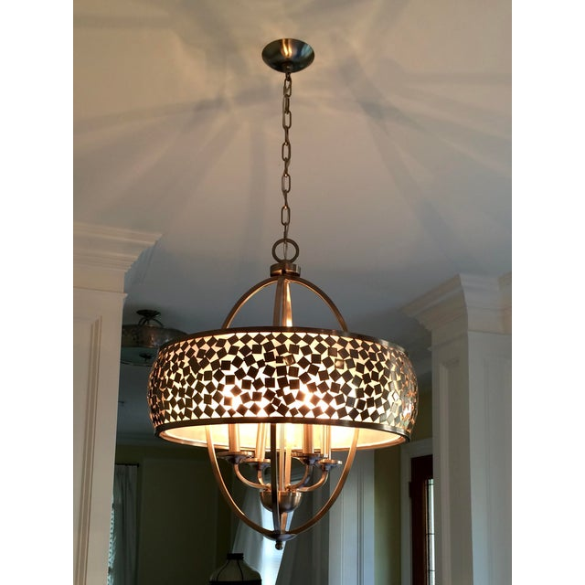 This unusual brushed steel chandelier has a double oval frame surrounded by a round outer frame embedded with hundreds of...