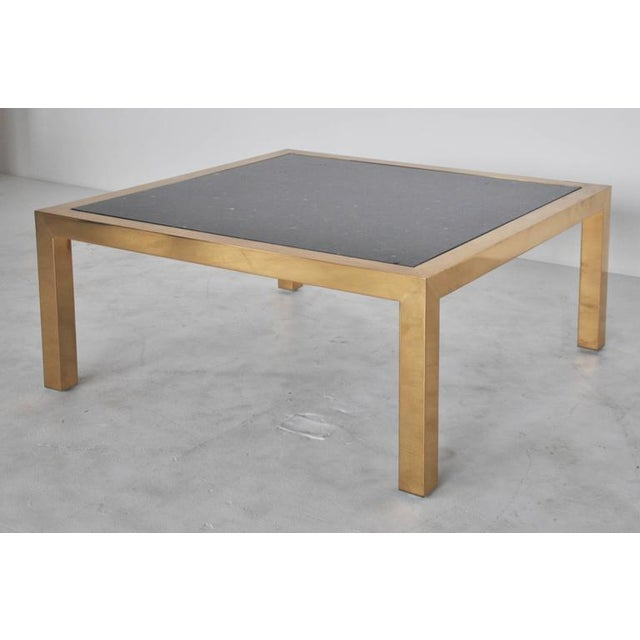 Brass frame coffee table with black granite top circa 1970s.