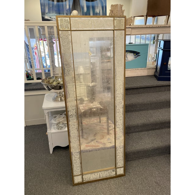 This is a beautiful floor-length mirror. It is an antique piece with a white gold foil backing the mirror. There is a...