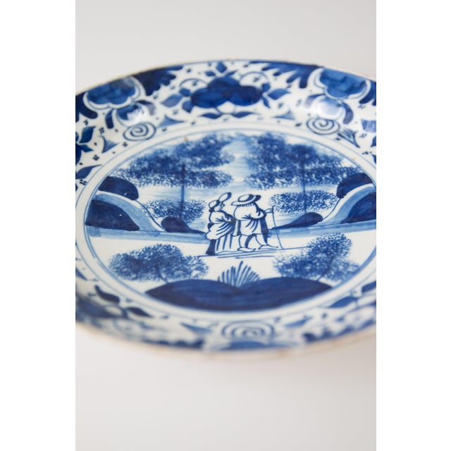 Exquisite 18th-Century Dutch Delft plate with a hand painted couple strolling in a landscape. The cobalt blue and white...