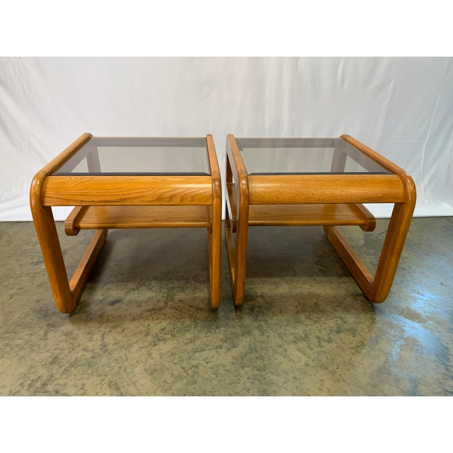 A pair of California design Mid-Century Modern Lou Hodges oak end tables. Each table has an inset smoked grey glass top...