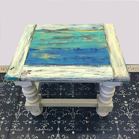 This charming hand-painted end table is looking for a good home. Its multicolored blue, teal and grey distressed finish...