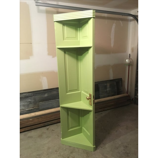 An old door was transformed in to a whimsical corner shelf and finished in a neutral green color. Original brass hardware...