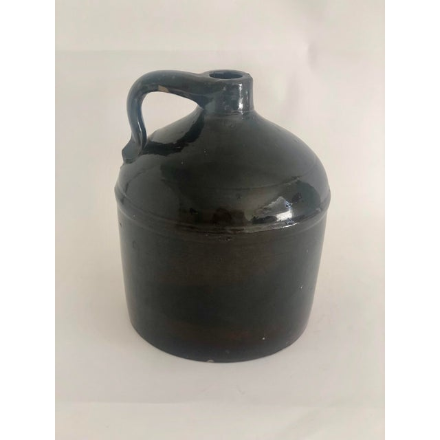 100 year old farmhouse stoneware jug sourced in Vermont originally used for food storage. In classic brown glaze with aged...