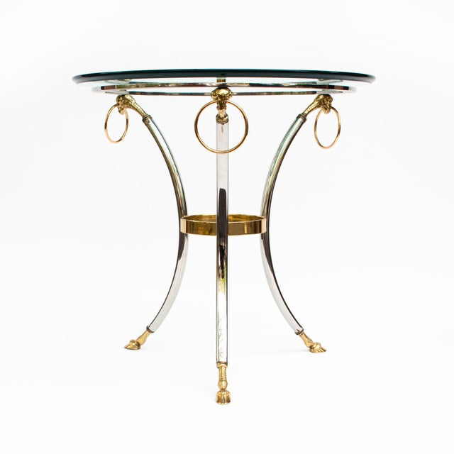 Stunning Hollywood Recency style, high quality brass and chrome round side table with a thick beveled glass top. The...