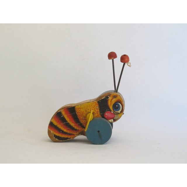 """Antique """"Buzzy Bee"""" pull-style toy with wheels and wings that move when the toy is pulled. Some losses to paper backing...."""