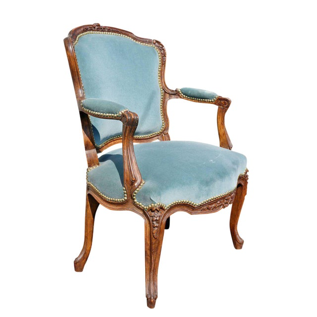 Carved shaped crestrail and upholstered back and seat raised on cabriole legs.