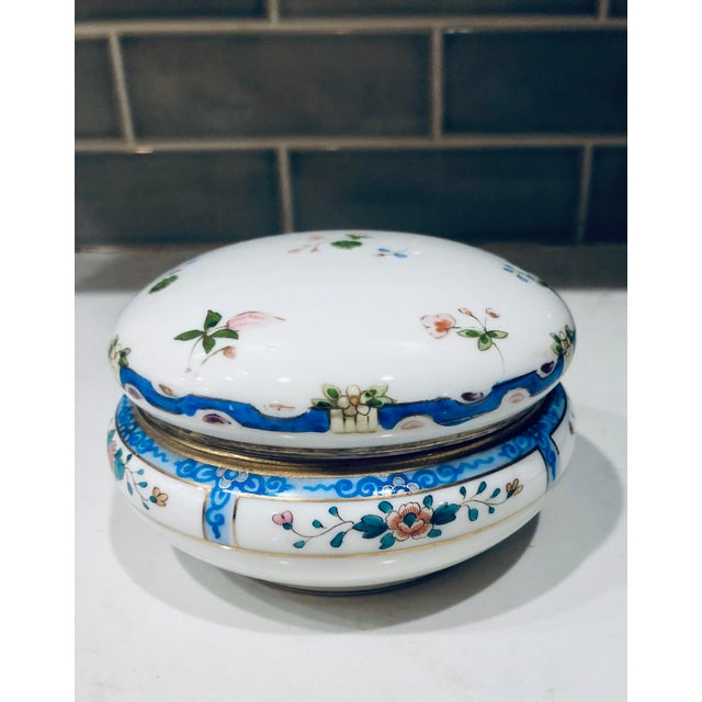 Lovely feminine china box. Hand painted in florals with a blue border.