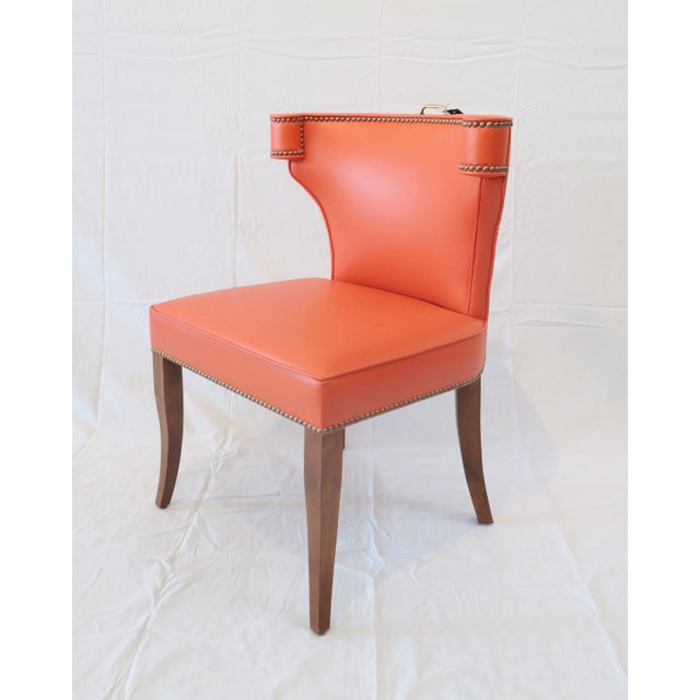 The Martin and Brockett Hale chair has a fully upholstered curved back, trimmed in brass nail heads. Oak saber legs with...