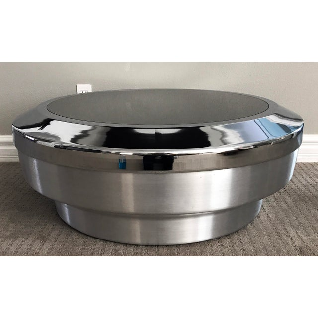 A stunning round, drum/canister coffee table designed by GJ Neville. This stunning coffee table features a brushed chrome...