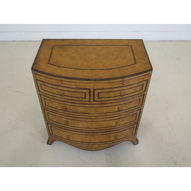 Maitland Smith bow front leather bachelor chest. Features quality tooled leather surface and pull out slide on top. Top of...