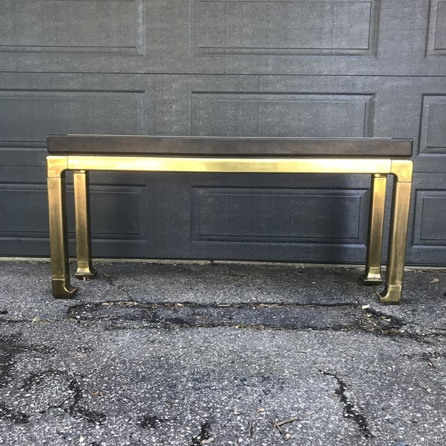 Extremely heavy table with brass base. Brown leather top with brass trim accent. Would complement any mid century modern,...