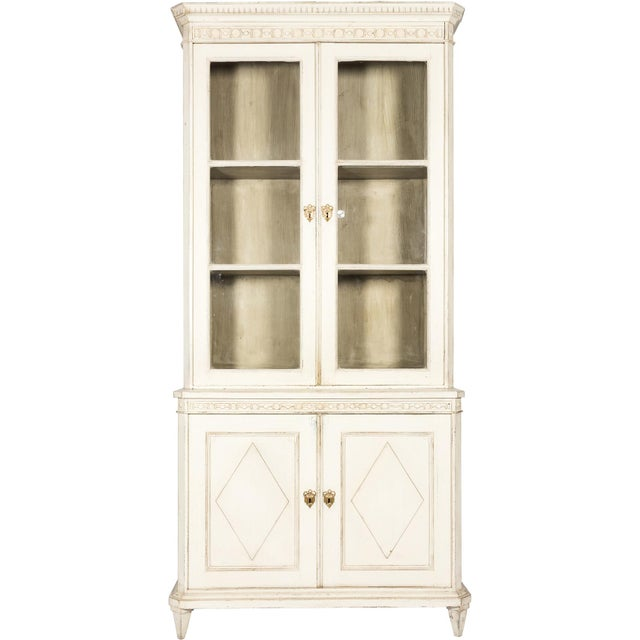 Sweden, 19th century. A white-painted Gustavian-style glass-fronted book cabinet, carved border, 2 lower doors with...